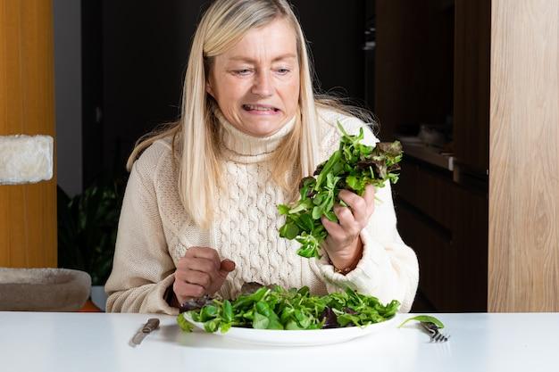 Blonde vrouw van middelbare leeftijd met ontevreden gelaatsuitdrukking salade eten in de keuken, gezonde voeding en dieet concept Premium Foto