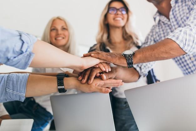 Blonde vrouwelijke beambte met glimlach opzoeken terwijl hand in hand met collega's. binnenportret van vrienden klaar om gezamenlijk werkproject te starten. Gratis Foto