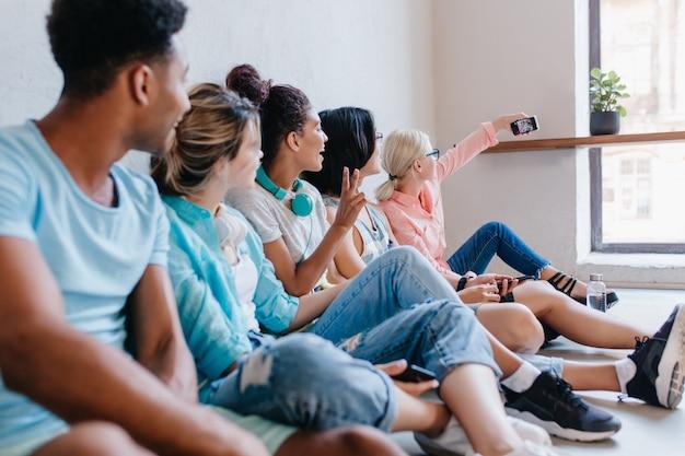 Blonde vrouwelijke student in glazen zittend naast raam en selfie maken met klasgenoten. portret van vrienden die een blond meisje kijken en een foto van hen nemen. Gratis Foto