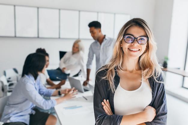 Blonde vrouwelijke uitvoerende poseren met glimlach en armen gekruist tijdens brainstorm met managers. indoor portret van europese student tijd doorbrengen in hal met aziatische en afrikaanse vrienden. Gratis Foto