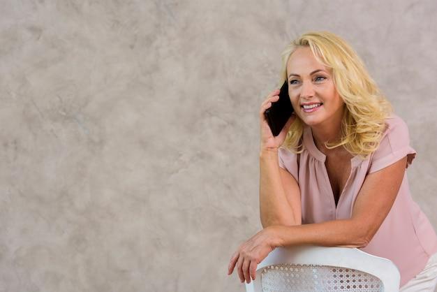 Blondedame die op de telefoon met exemplaarruimte spreken Gratis Foto
