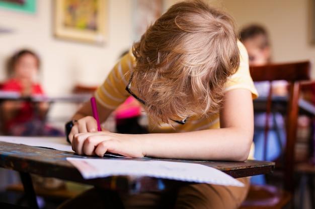 Blondejongen met glazen het trekken. groep basisschoolleerlingen in klaslokaal op kunstklasse Premium Foto