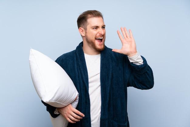 Blondeman in pyjama schreeuwen met wijd open mond Premium Foto
