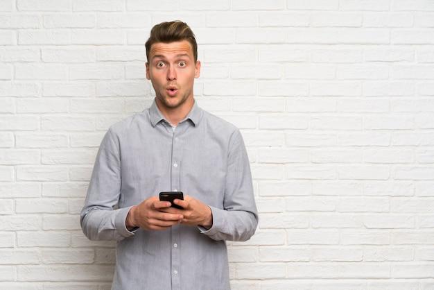 Blondeman over witte bakstenen muur verrast en een bericht verzenden Premium Foto