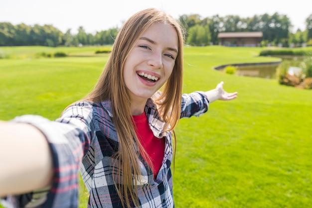 Blondemeisje die een selfie met een mooie achtergrond nemen Gratis Foto