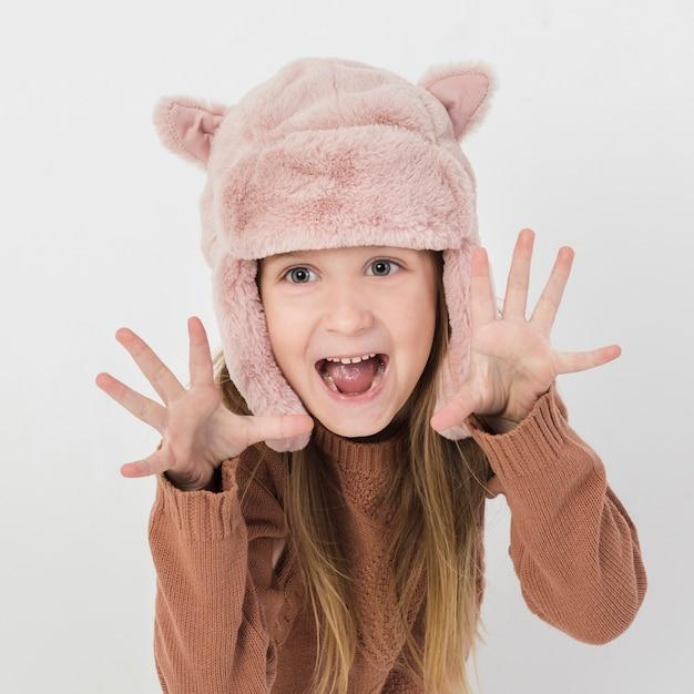 Blondemeisje die grappige gezichten met de winterhoed maken Gratis Foto