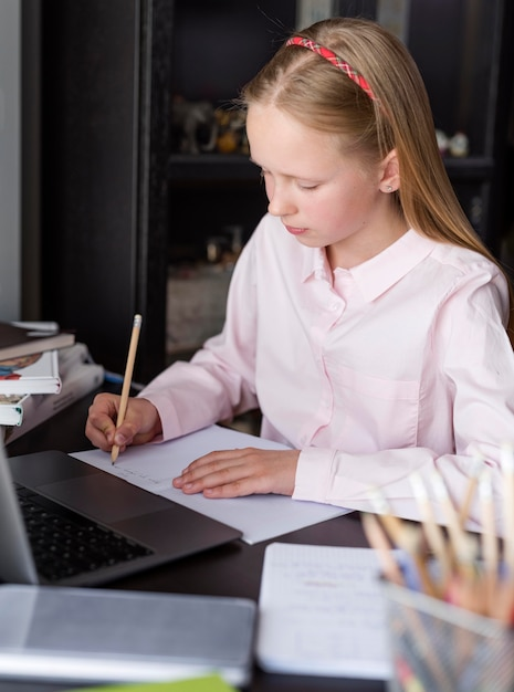 Blondemeisje die nota's in online klasse maken Gratis Foto