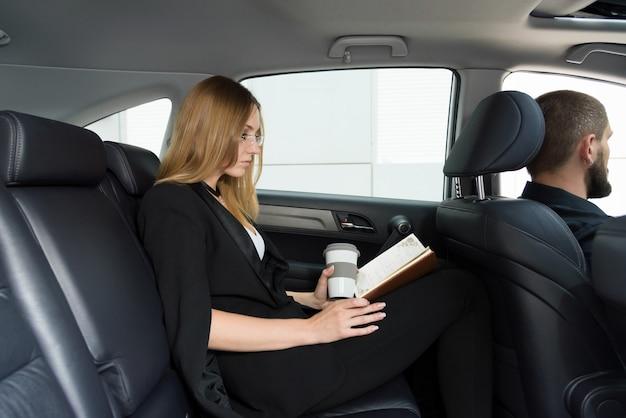 Blondemeisje in een auto met een bestuurder op de achterbank met een kop en een notitieboekje Premium Foto