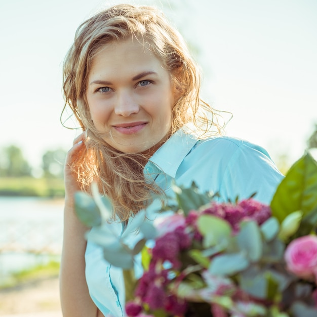 Blondemeisje met boeket in een blauwe kleding Premium Foto