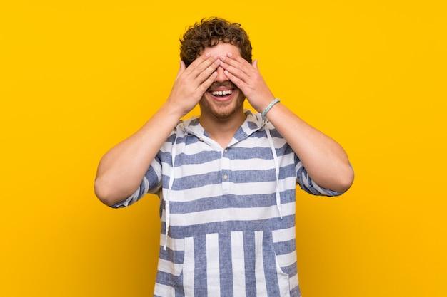 Blondemens die over gele muur ogen behandelen door handen. verrast om te zien wat er gaat gebeuren Premium Foto