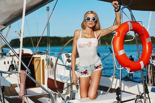 Blondemodelmeisje met perfect slank lichaam in borrels en t-shirt het stellen op een jachtschip Premium Foto