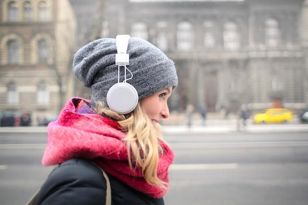 Blondevrouw die aan muziek op hoofdtelefoons luisteren Premium Foto