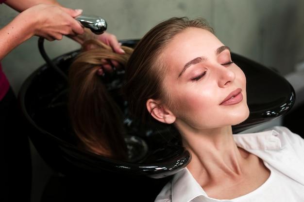 Blondevrouw die haar krijgen gewassen bij salon Gratis Foto