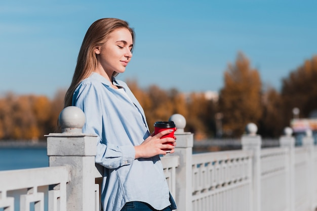 Blondevrouw die op traliewerk rusten en een koffiekop houden Gratis Foto