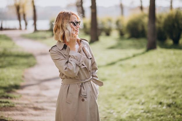Blondevrouw in laag buiten in park die telefoon met behulp van Gratis Foto