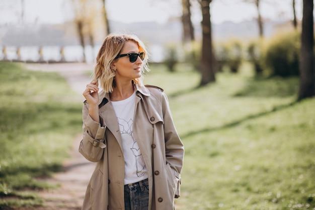 Blondevrouw in laag buiten in park Gratis Foto