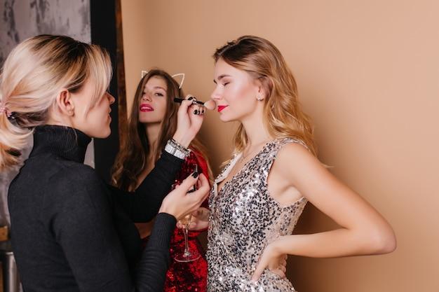 Blondevrouw in zwart overhemd die make-up voor krullend vrouwelijk model doen Gratis Foto