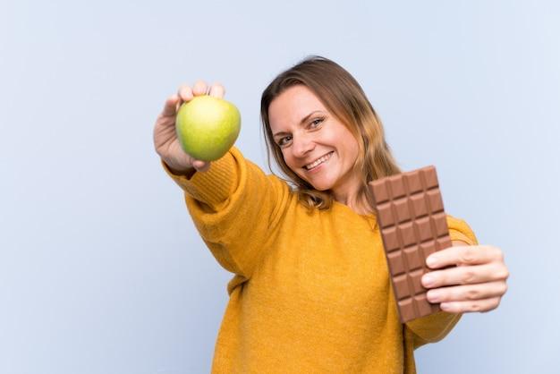 Blondevrouw over geïsoleerde blauwe muur die een chocoladetablet in één hand en een appel in de andere nemen Premium Foto
