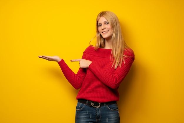 Blondevrouw over gele muurholding denkbeeldige copyspace Premium Foto