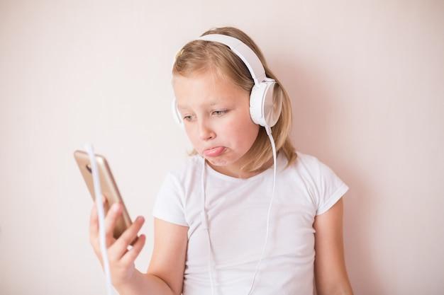 Blondie tienermeisje dat met oortelefoons aan muziek luistert Premium Foto