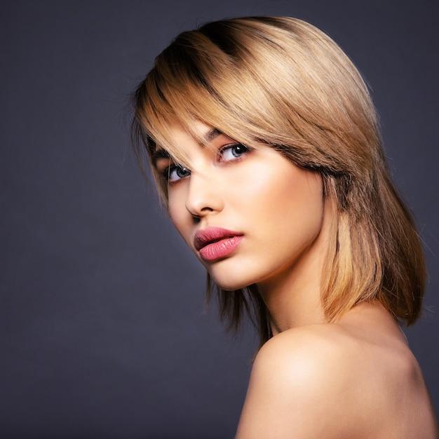 Blone vrouw met kort haar, pony. sexy blonde vrouw. aantrekkelijk blond model met blauwe ogen. mannequin met een rokerige make-up. closeup portret van een mooie vrouw. creatief kort kapsel. Gratis Foto