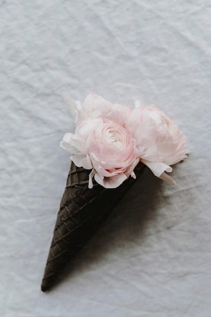 Blozen ranunculus in een wafelkegel Gratis Foto