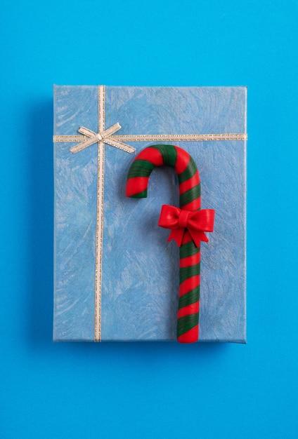 Blue christmas gift box versierd met een riet van het suikergoed op de blauwe achtergrond Gratis Foto