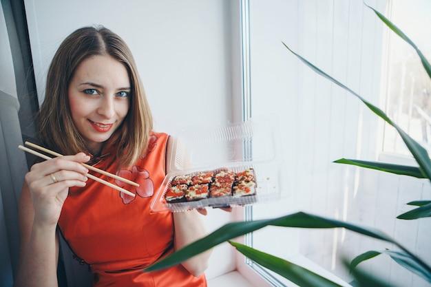 Blueeyed kaukasisch meisje dat in traditionele chinese kleding sushistokken eet. Premium Foto