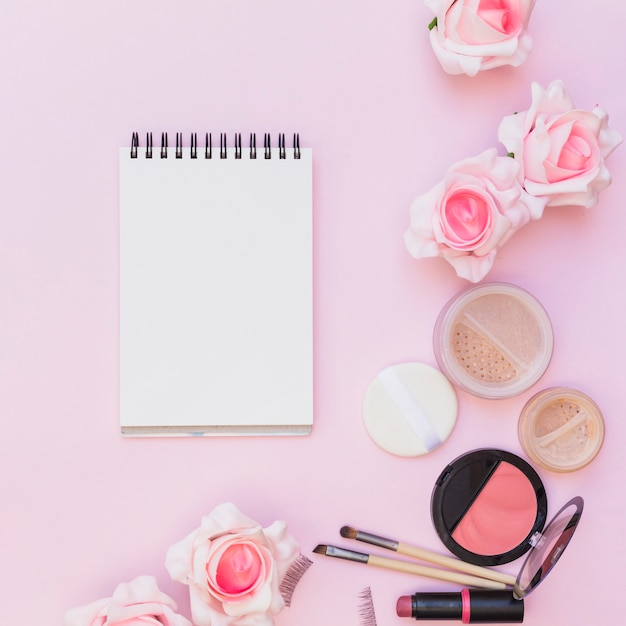 Blusher; lippenstift; spons; make-upborstel met rozen op roze achtergrond Gratis Foto
