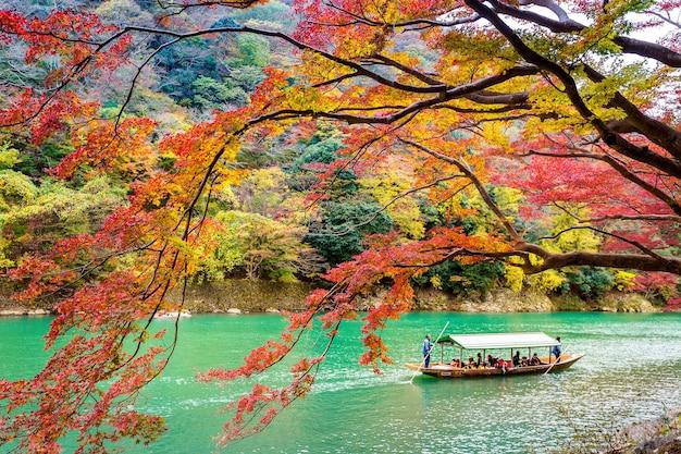 Boatman punteren de boot op de rivier. arashiyama in de herfstseizoen langs de rivier in kyoto, japan Gratis Foto