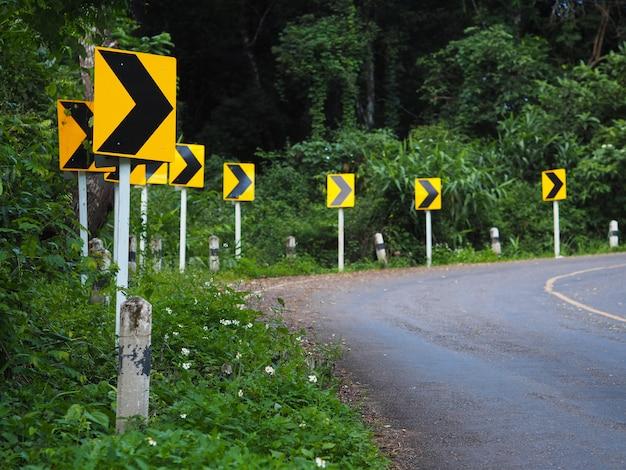 Bochtwaarschuwingsbord op kronkelende weg in het bos om voorzichtig te rijden. Premium Foto