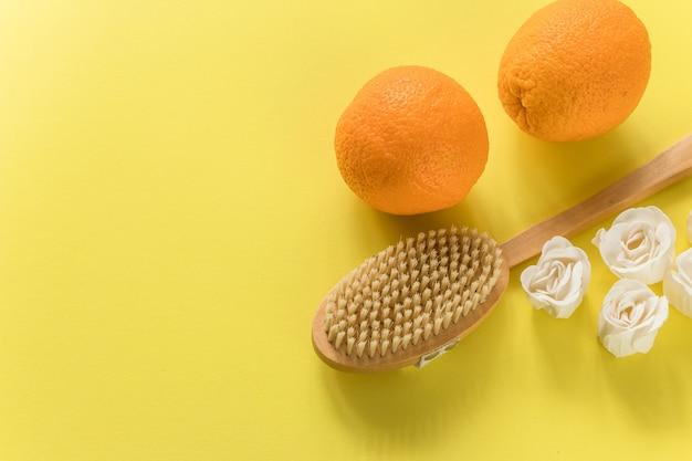 Body brush met grote sinaasappels en witte zeep in roosvorm voor anti-cellulitis massage op gele muur. plat ontwerp met kopie ruimte. cactus exfoliërende borstel voor lichaamsverzorging Premium Foto