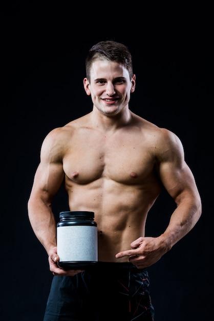 Bodybuilder die een zwart plastic weiproteïne van het kruik leeg wit etiket houden en naar het met zijn hand richten die op donkere muur wordt geïsoleerd Premium Foto