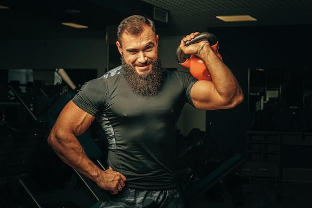 Bodybuilder die oefeningen met domoren in een donkere gymnastiek doen Premium Foto