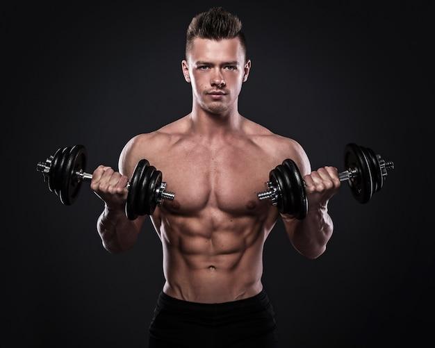 Bodybuilder doet oefeningen met halters Premium Foto