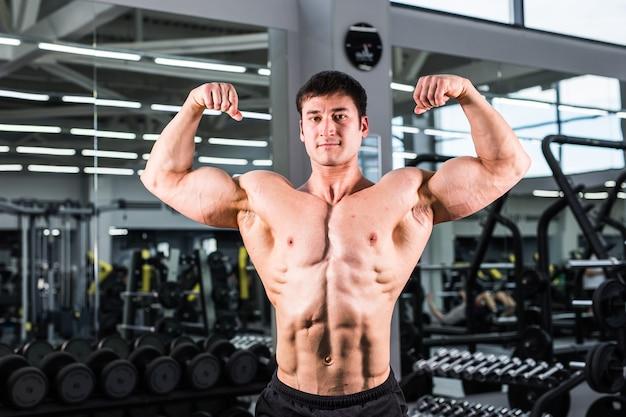 Bodybuilder man met perfecte biceps, triceps en borst in de sportschool. Premium Foto