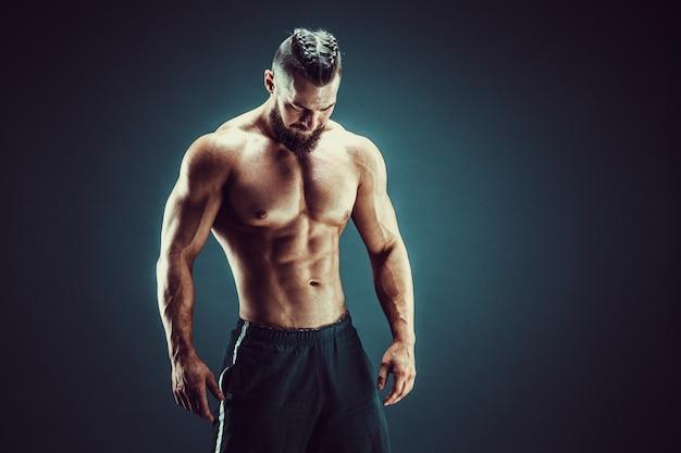 Bodybuilder poseren. fitness gespierde man op donkere achtergrond. Premium Foto