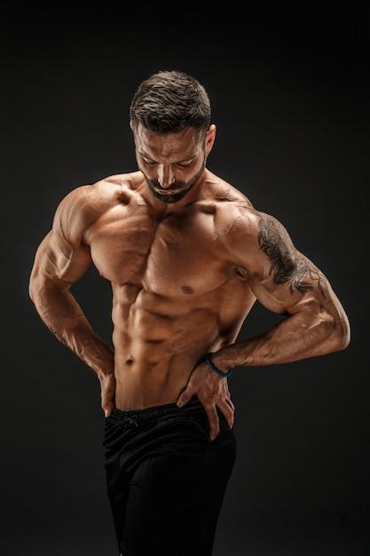 Bodybuilder poseren. fitness gespierde man op donkere muur. Premium Foto