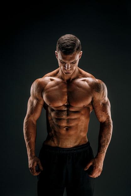 Bodybuilder poseren fitness gespierde man op donkere scène Premium Foto