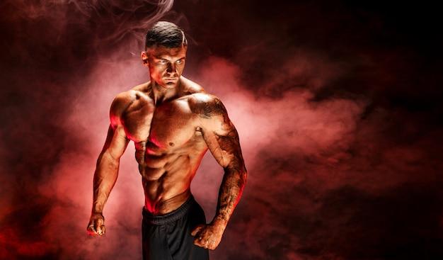 Bodybuilder poseren fitness getatoeëerd gespierde man op rode rook scène Premium Foto