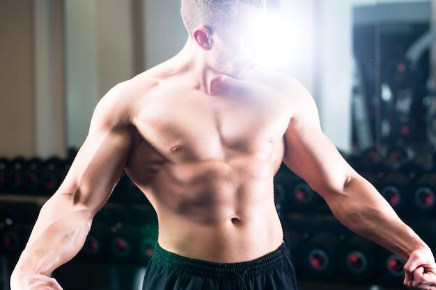 Bodybuilder poseren in de sportschool Premium Foto