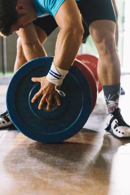 Bodybuilding concept met man en gewichtsplaten Gratis Foto