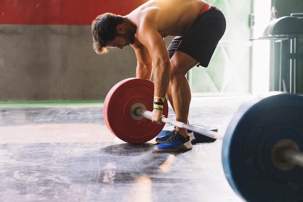Bodybuilding concept met man montage barbell Gratis Foto