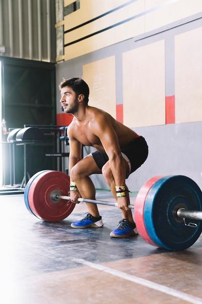 Bodybuilding concept met man uit te werken met barbell Gratis Foto