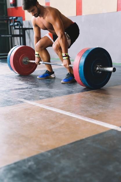 Bodybuilding concept met sterke man over het opheffen van barbell Gratis Foto