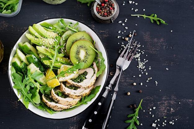 Boeddha schaal met kipfilet, avocado, komkommer, verse rucola salade en sesam. Premium Foto