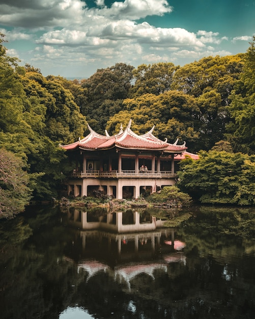Boeddhistische tempel boven het meer omgeven door bomen, shinjuku gyoen national garden, tokyo Gratis Foto