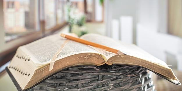Boek bijbel met potlood close-up, op de achtergrond van een prachtig terras. ochtend tijd. Gratis Foto