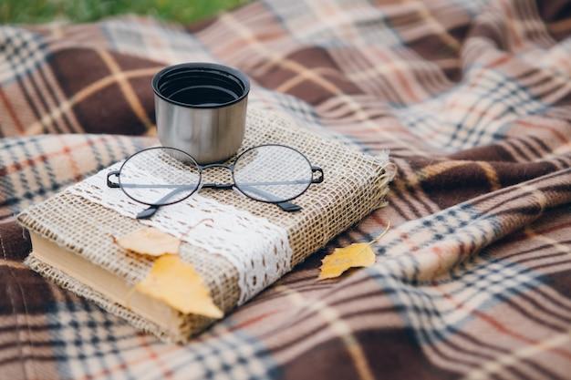 Boek, glazen en hete thee uit een thermoskan liggen op een deken Premium Foto