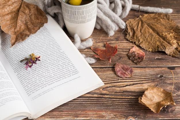 Boek in de buurt van citroenthee en herfstbladeren Gratis Foto